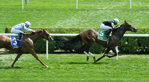 Jockey Jose Lezcano riding Thieves Guild, right, races towards the finish line for a first place as jockey Joel Rosario riding Free as a Bird comes in second in the third race at the Saratoga Race Course on Sunday, August 2, 2015, in Saratoga Springs, N.Y.    (Paul Buckowski / Times Union) Photo: PAUL BUCKOWSKI / 10032858A