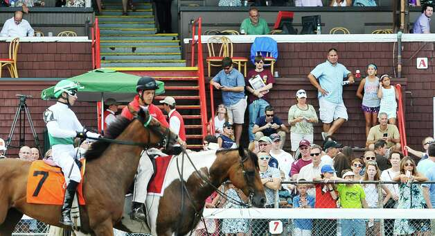 Racing fans watch as the jockeys and horses parade past them before the start of the fourth race at the Saratoga Race Course on Sunday, August 2, 2015, in Saratoga Springs, N.Y.   (Paul Buckowski / Times Union) Photo: PAUL BUCKOWSKI / 10032858A