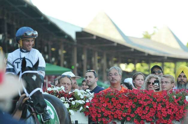 Racing fans look on as Jockey Javier Castellano sits atop Stop Charging Maria in the winners circle following the tenth race at the Saratoga Race Course on Sunday, August 2, 2015, in Saratoga Springs, N.Y.   (Paul Buckowski / Times Union) Photo: PAUL BUCKOWSKI / 10032858A