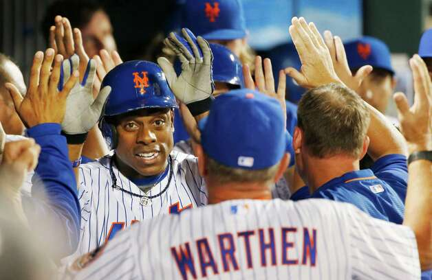 New York Mets Curtis Granderson, left, greets pitching coach Dan Warthen, foreground, in the dugout after hitting a third-inning, two-run, home run during a baseball game in New York on Sunday, Aug. 2, 2015. (AP Photo/Kathy Willens) ORG XMIT: NYM104 Photo: Kathy Willens / AP