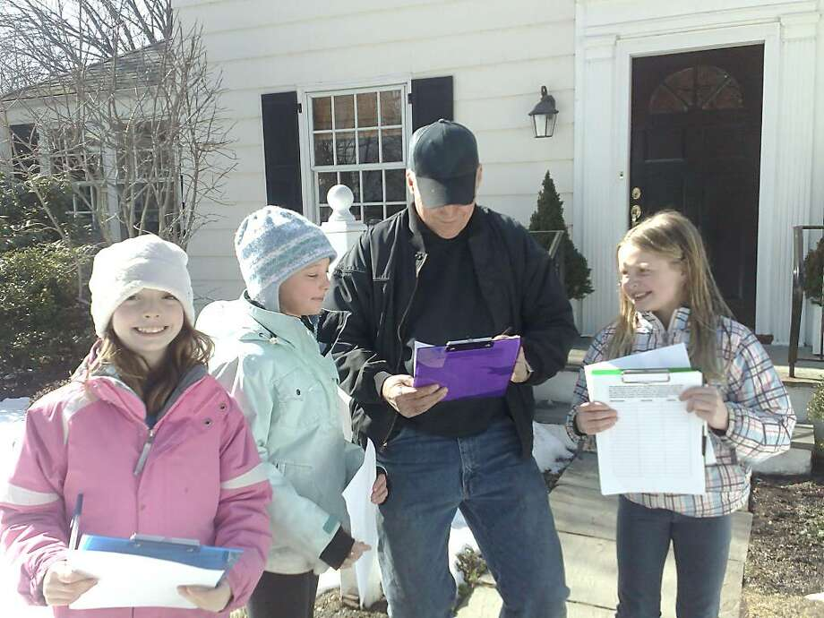 "Gigi Jervis, left, and her fellow third graders, Harper Thorson in blue and Alexandre Fiore, obtained the signature of Ray Hubbard on Perryride Road for the Jervis ""Mandate a Mile"" petition Photo: Contributed Photo / Greenwich Citizen"