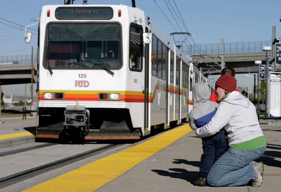 Denver has something that San Antonio needs to connect its locals to their downtown — light rail. Jill Cooper, right, holds her 3-year-old son, Wyatt, as a Regional Transportation Distirct light rail train arrives at the Broadway station in south Denver in 2006. Photo: David Zalubowski /AP / AP