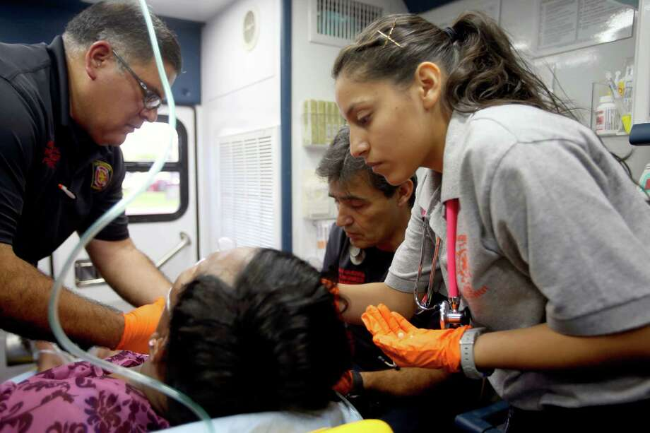 Edison High School student Gisel Garcia, a student in the fire sciences magnet program, worked Tuesday with a San Antonio Fire Department EMT crew as they treat a patient. Photo: William Luther /San Antonio Express-News / © 2015 San Antonio Express-News