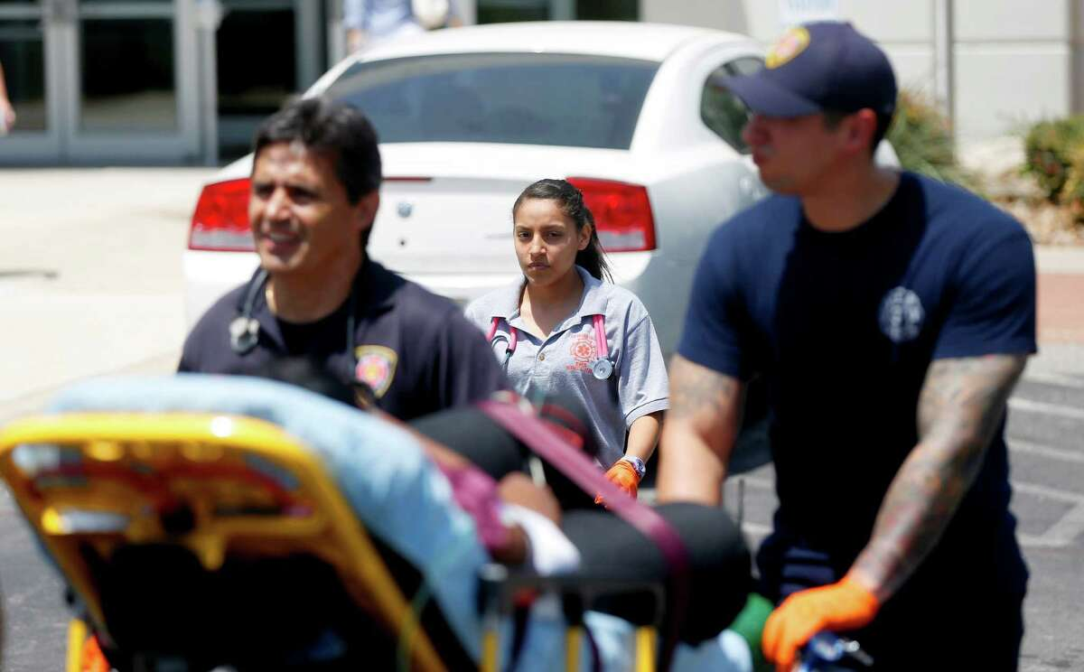 Edison High School student Gisel Garcia, a student in the fire sciences magnet program, works Tuesday July 28, 2015, with an SAFD EMT crew as they treat a patient.