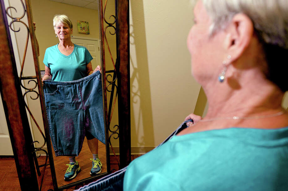 Ruby Dailey holds an old pair of shorts in front of the mirror to show how much weight she has lost. Dailey said she has lost 100 pounds by eating healthy and exercising.    Photo taken Thursday, July 30, 2015  Guiseppe Barranco/The Enterprise Photo: Guiseppe Barranco, Photo Editor