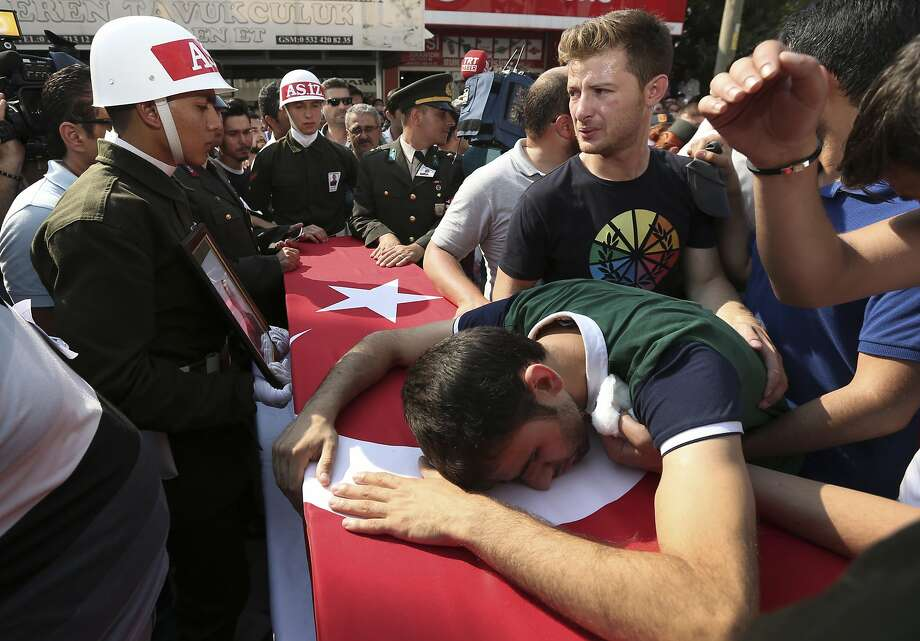 A relative cries over the Turkish flag-draped coffin of Turkish soldier Kagan Kandemir, during his funeral in the town of Civril, Turkey, Friday, July 31, 2015. Kandemir, was one of the three Turkish troops that were killed on July 30 when Kurdistan Workers' Party, or PKK militants opened fire on their convoy in the southeastern province of Sirnak, according to the army. (AP Photo/Depo Photos)  TURKEY OUT Photo: Associated Press