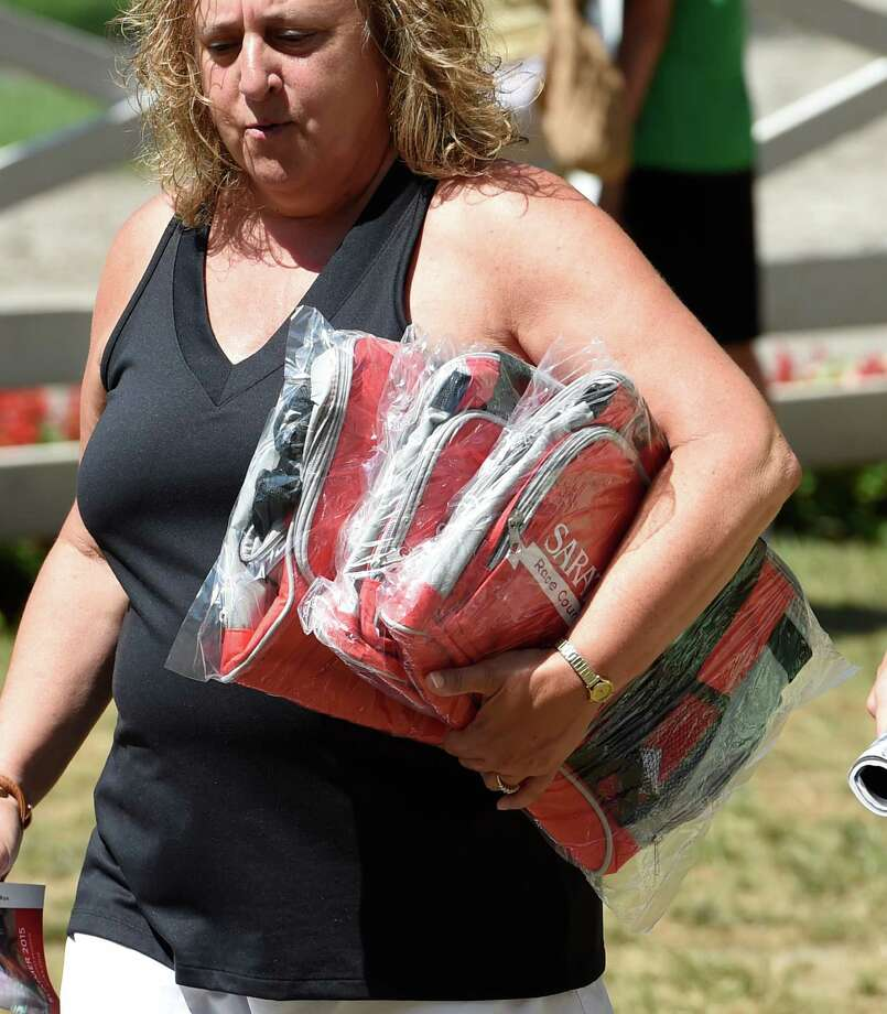 Racing patrons haul away arm loads of cooler bags, the most recent giveaway of the Saratoga season Monday morning Aug. 3, 2015 at the Saratoga Race Course in Saratoga Springs, N.Y.  (Skip Dickstein/Times Union) Photo: SKIP DICKSTEIN / 10032868A