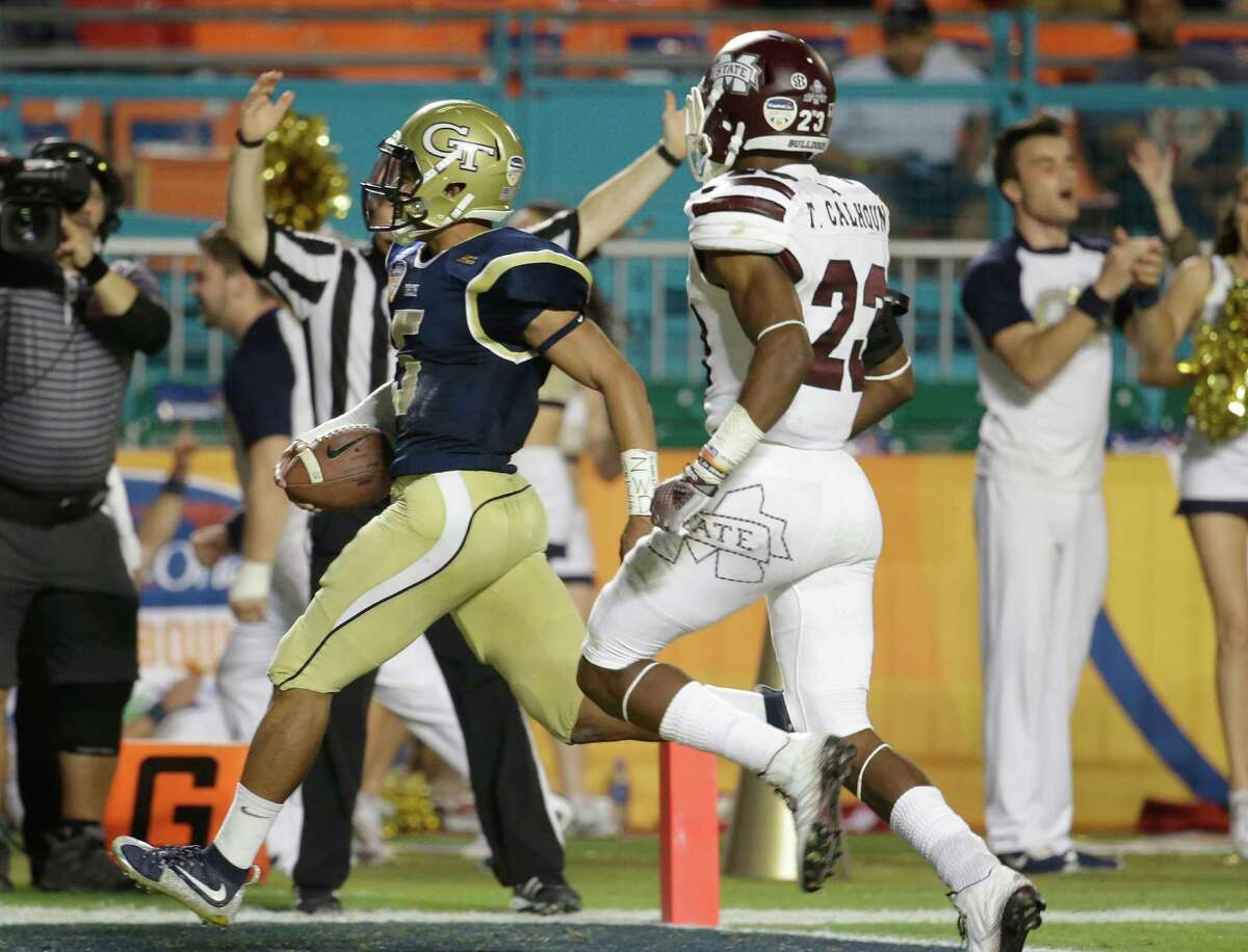 Georgia Tech quarterback Justin Thomas, left, scores a touchdown in front of Mississippi State defensive back Taveze Calhoun (23) in the second half of the Orange Bowl NCAA college football game, Wednesday, Dec. 31, 2014, in Miami Gardens, Fla.
