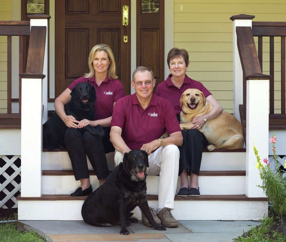 Jennifer Hill with her parents Carol and Henry Hill (retired company founders) and a few of the familyís dogs. Photo: Contributed Photo