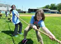 Mariah Hughes, foreground, 9, and Shayna Lieman, 8, background along with their fellow campers, take part in a tug-of-war at the Albany Police Athletic League's  sixth annual Summer Camp Olympics at Veterans Memorial Park on Monday, Aug. 3, 2015, in Albany, N.Y.  The olympics brings together children in the various PAL summer camps throughout the city.   (Paul Buckowski / Times Union)