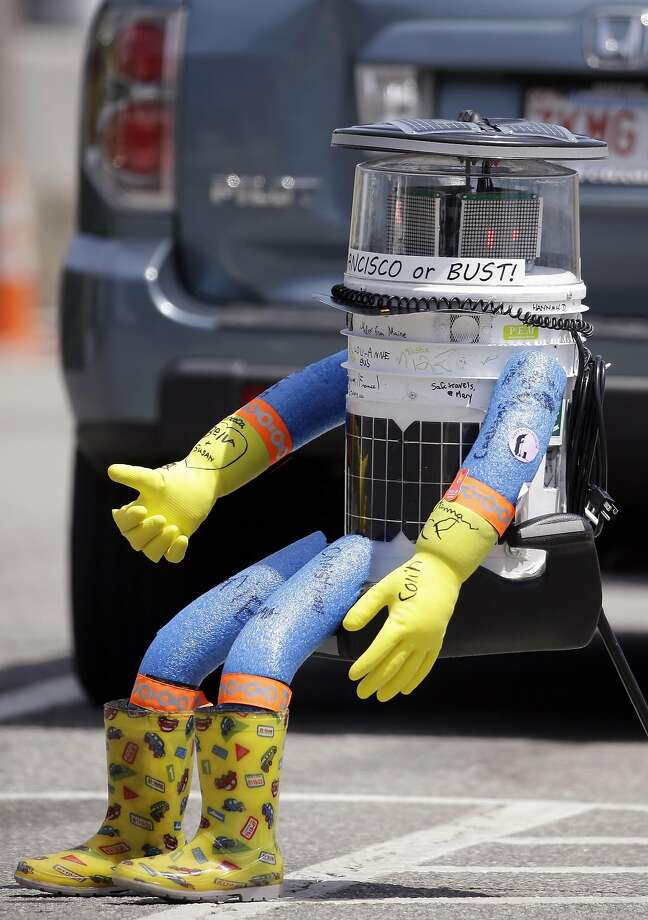 HitchBOT, a hitchhiking robot, waits for a passing motorist to pick it up Friday, July 17, 2015, in Marblehead, Mass. HitchBOT is beginning its' first cross-country hitchhiking trip of the U.S., in Marblehead with a final destination goal of reaching San Francisco. (AP Photo/Stephan Savoia) Photo: Stephan Savoia, Associated Press