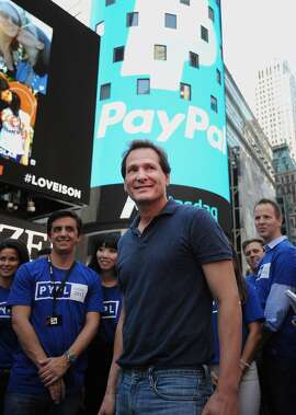Dan Schulman, president and chief executive officer of PayPal Holdings Inc., center, stands for a photograph with his employees using a mobile device after the release of the company's initial public offering (IPO) outside of the Nasdaq MarketSite in New York, U.S., on Monday, July 20, 2015. PayPal Holdings Inc. shares rose as much as 11 percent in their market debut after separating from EBay Inc. Photographer: Louis Lanzano/Bloomberg *** Local Caption *** Dan Schulman