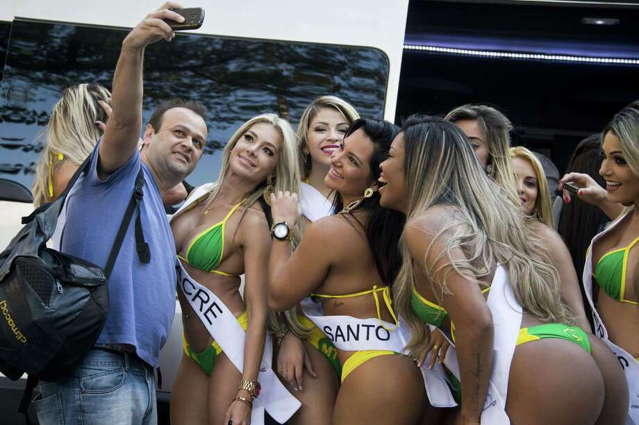 A man takes a selfie with candidates to the Miss Bumbum Brazil 2015 pageant at Paulista Avenue in Sao Paulo, Brazil during an event to promote the contest. Photo: NELSON ALMEIDA, AFP / Getty Images / AFP