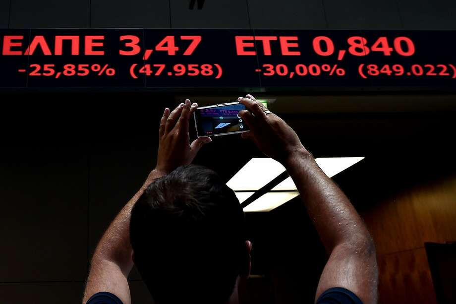 A man takes a snapshot of a stock index in the lobby of the Athens Stock Exchange in Athens on August 3, 2015. Greece's stock exchange reopened August 3 with a drop of more than 22 percent after a five-week shutdown imposed by the country's debt crisis and capital controls, with the nation's outflow-hit lenders leading the way. The ATHEX plunged to 615.72 points a few minutes after opening at 7:30 GMT, down 22.82 percent from its June 26 close. AFP PHOTO / ARIS MESSINISARIS MESSINIS/AFP/Getty Images Photo: Aris Messinis, AFP / Getty Images