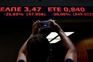 Greece's market reopens; stocks plunge - Photo