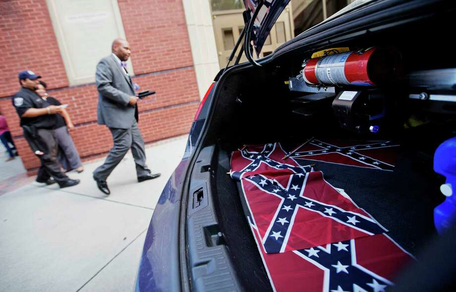 Confederate flags discovered near the church where Martin Luther King Jr. preached sit in the back of a police car last month. Readers continue to debate whether the flags should be removed from public places. Photo: David Goldman /Associated Press / AP