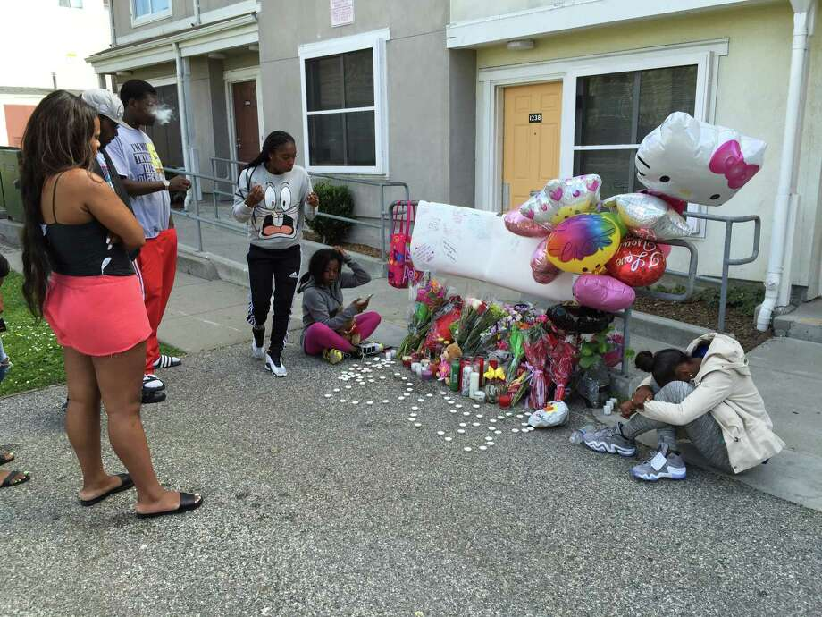 Friends and family members of 19-year-old Ranisha Raven gather near a memorial of flowers and candles Monday near where the young woman was gunned down Saturday night. Police have not identified or arrested any suspects in the killing. Photo: Evan Sernoffsky / Evan Sernoffsky / ONLINE_YES