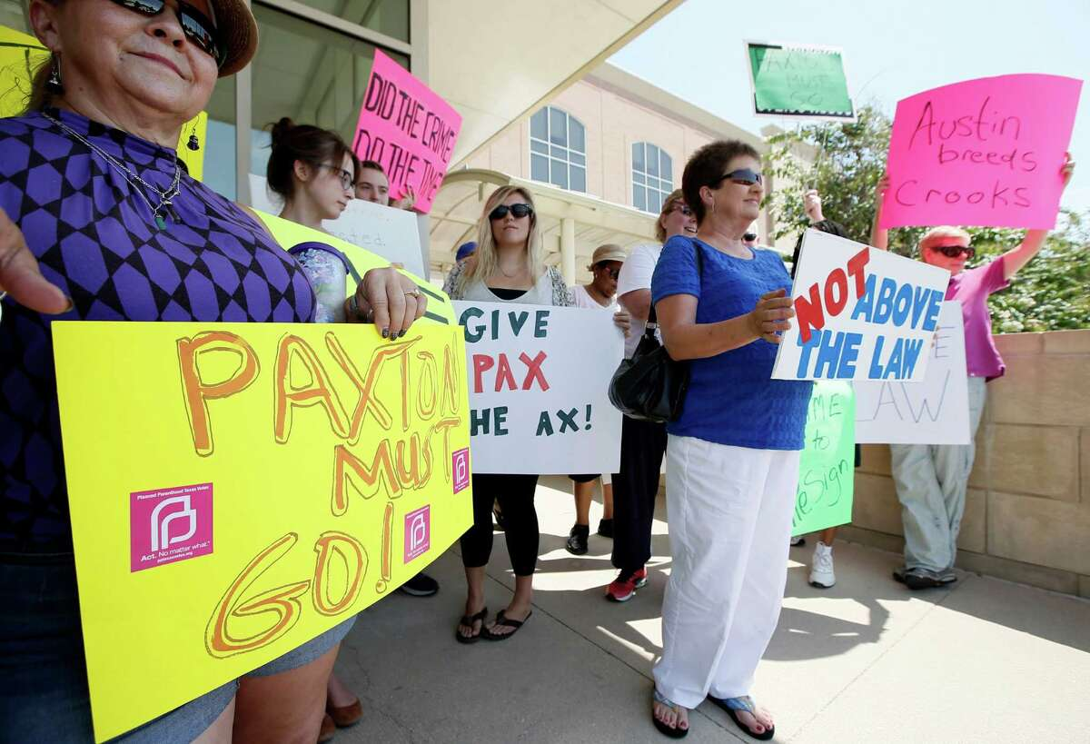 Protesters against Texas Attorney General Ken Paxton hold signs as they stand outside the Collin County Courthouse, Monday, Aug. 3, 2015, in Plano, Texas. Paxton turned himself in Monday to face charges that he misled investors and didn't disclose money he made for referring financial clients as part of his private business before becoming the state's top lawyer in January. (AP Photo/Tony Gutierrez)