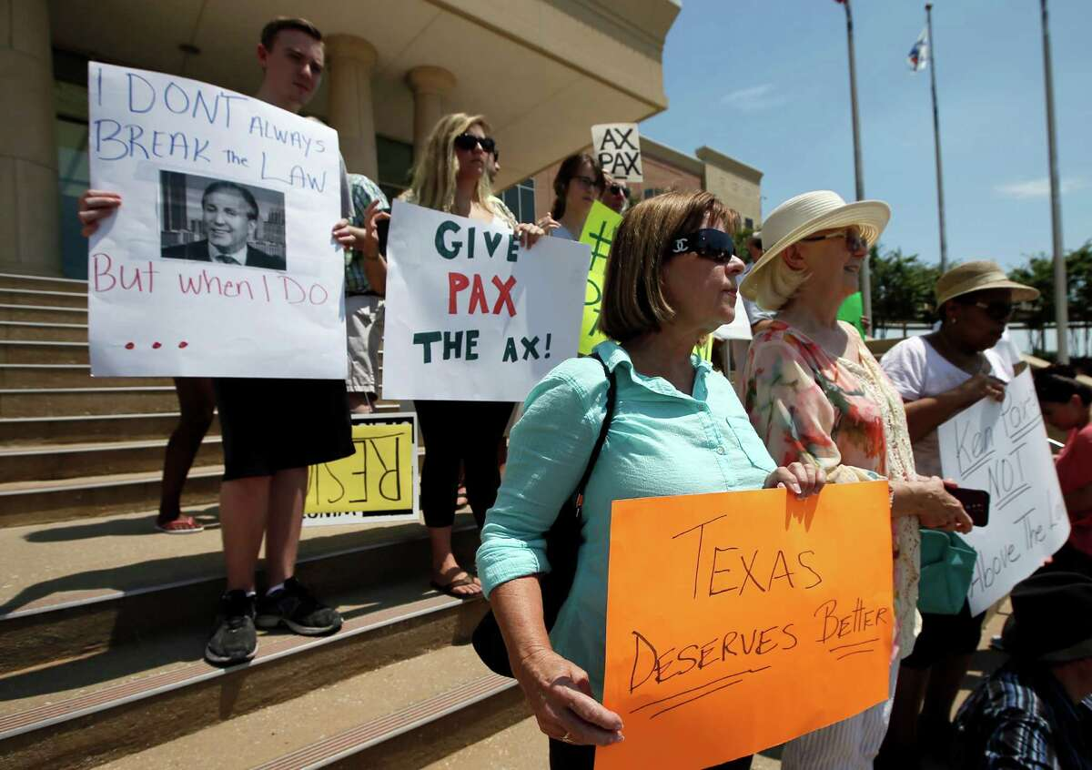 Protesters call for the resignation of Texas Attorney General Ken Paxton as they stand on the Collin County Courthouse steps, Monday, Aug. 3, 2015, in Plano, Texas. Paxton turned himself in Monday to face charges that he misled investors and didn't disclose money he made for referring financial clients as part of his private business before becoming the state's top lawyer in January. (AP Photo/Tony Gutierrez)