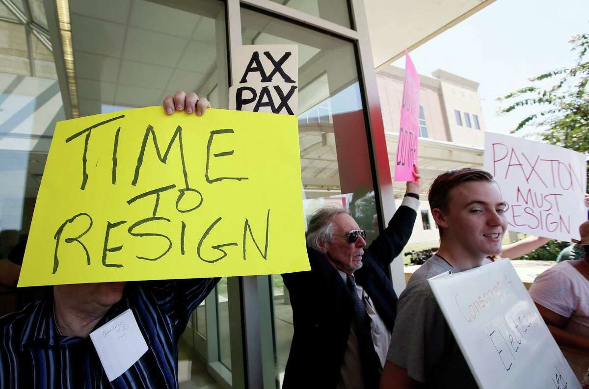 Protesters calling for Texas Attorney General Ken Paxton to resign hold signs as they stand outside the Collin County Courthouse, Monday, Aug. 3, 2015, in Plano, Texas. Paxton turned himself in Monday to face charges that he misled investors and didn't disclose money he made for referring financial clients as part of his private business before becoming the state's top lawyer in January. (AP Photo/Tony Gutierrez)