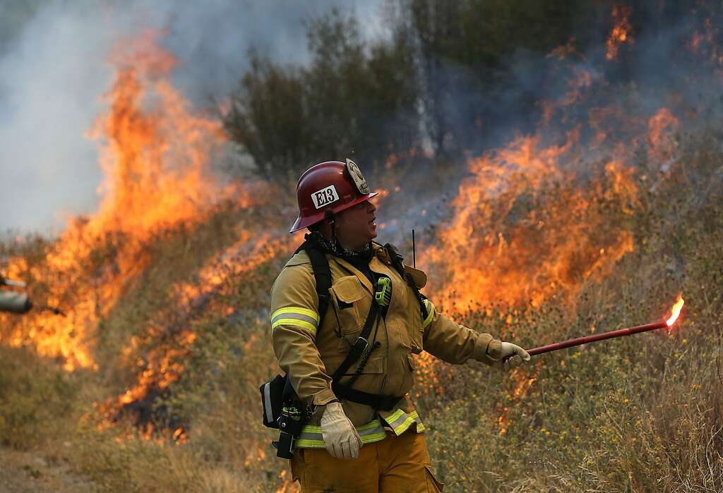 A Long Beach Fire Department fire captain uses a flare to burn dry grass during a backfire operation to head off the Rocky Fire on August 3, 2015 near Clearlake, California. Nearly 3,000 firefighters are battling the Rocky Fire that has burned over 60,000 acres has forced the evacuation of 12,000 residents in Lake County. The fire is currently 12 percent contained and has destroyed at least 14 homes. 6,300 homes are threatened by the fast moving  blaze. Photo: Justin Sullivan, Getty Images