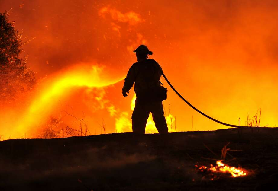 Firefighter Joe Darr douses flames of the Rocky fire along Highway 20 near Clearlake, California on August 2, 2015. Thousands of firefighters battled raging wildfires on August 2 in drought-parched California, where officials evacuated entire neighborhoods and closed miles of highway in the path of the inferno, which has claimed at least one life. AFP PHOTO / JOSH EDELSONJosh Edelson/AFP/Getty Images Photo: Josh Edelson, AFP / Getty Images