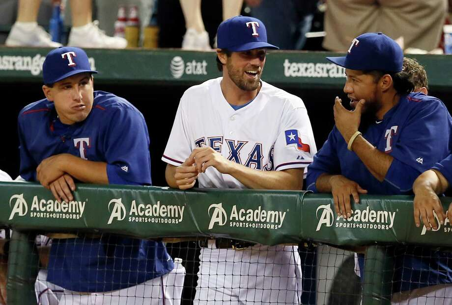 Texas Rangers pitchers Derek Holland, left, and Yovani Gallardo, right, talk with their newly acquired teammate Cole Hamels, center, in the seventh inning of a baseball game against the San Francisco Giants Friday, July 31, 2015, in Arlington, Texas. (AP Photo/Tony Gutierrez) Photo: Tony Gutierrez, Associated Press / AP