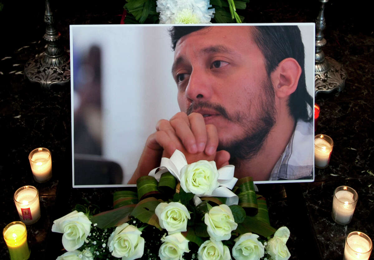 A photograph of murdered photojournalist Ruben Espinosa sits among flowers and candles in front of his casket inside a funeral home before his wake begins in Mexico City, Monday, Aug. 3, 2015. With an investigation barely underway, Mexican journalist protection groups are already expressing fears that authorities won't consider Espinosa's brutal killing as being related to his work - even though he fled the state he covered fearing for his safety. Espinosa, 31, worked for the investigative magazine Proceso and other media in Veracruz state. (AP Photo/Marco Ugarte)