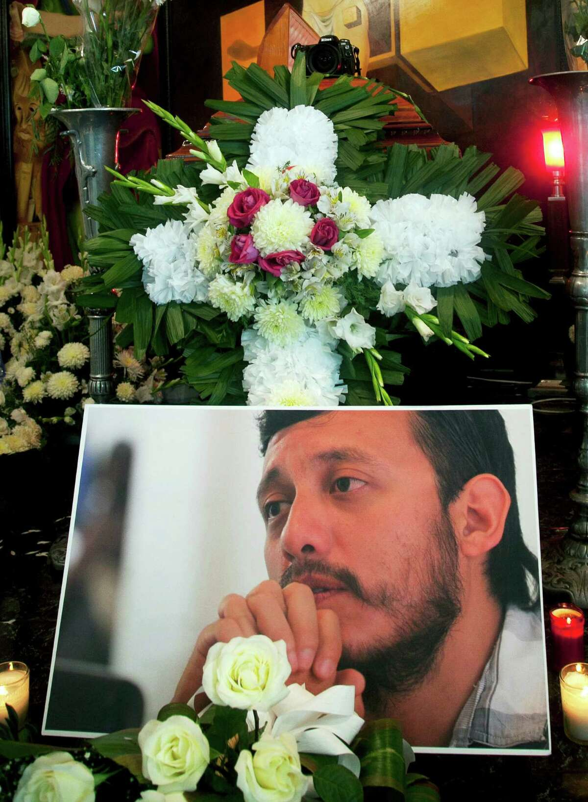 A photo of slain photojournal- ist Ruben Espinosa is in front of his casket in a funeral home in Mexico City.