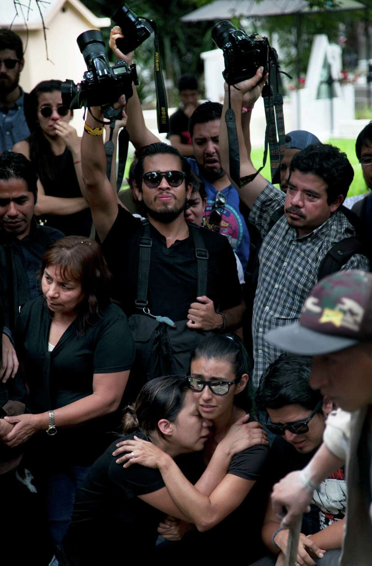Family and friends mourn during the funeral of murdered photojournalist Ruben Espinosa in Mexico City, Monday, Aug. 3, 2015. With an investigation barely underway, Mexican journalist protection groups are already expressing fears that authorities won't consider Espinosa's brutal killing as being related to his work - even though he fled the state he covered fearing for his safety. Espinosa, 31, worked for the investigative magazine Proceso and other media in Veracruz state. (AP Photo/Marco Ugarte)
