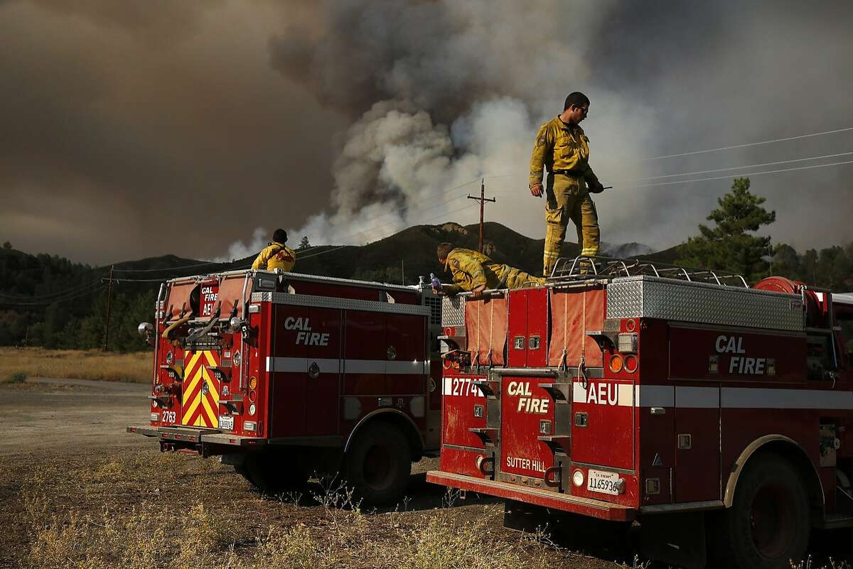 Cal Fire Amador firefighters Zachary Brenner, from right, Donald Ghormley, Fernando Solis take a break after a full shift of fighting the fire as the Rocky Fire burns off of highway 20 behind them August 3, 2015 in Lake County, Calif.