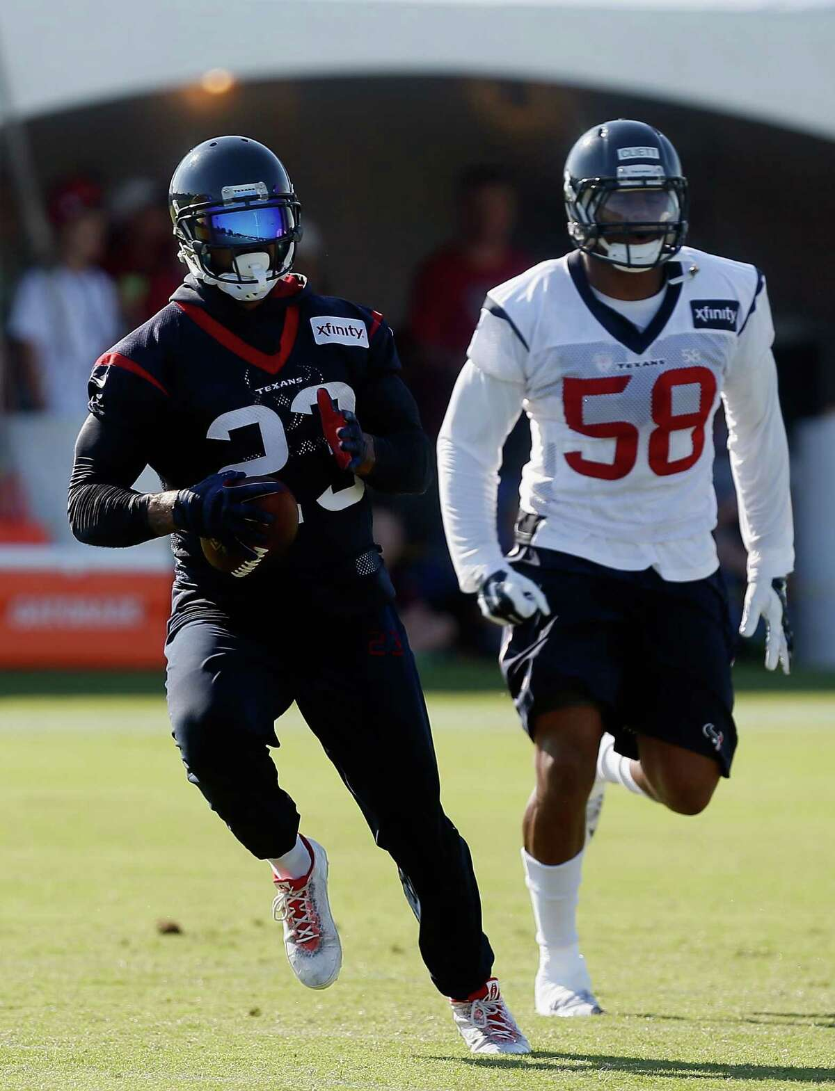 Houston Texans running back Arian Foster (23) makes a catch as aHouston Texans outside linebacker Reshard Cliett (58) defends during an NFL football training camp at the Methodist Training Center on Sunday August 2, 2015 in Houston.