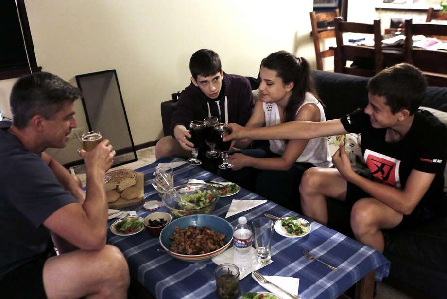 Evgeny Kulikov, dining with his children, from left, Tani, 21, Stefania, 17, and Martin, 13, isn't happy that the city suggested he rent a Treasure Island home that has only one shower. Photo: Dorothy Edwards, The Chronicle