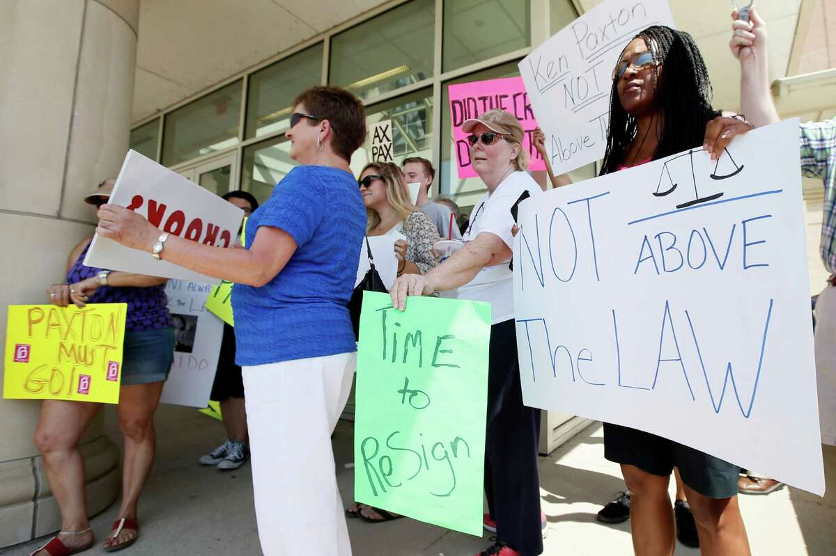 Protesters demonstrate against Attorney General Ken Paxton outside the Collin County Courthouse as he was being booked Monday.
