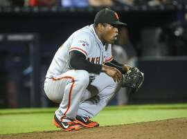 San Francisco Giants relief pitcher Santiago Casilla (46) reacts after giving up a two-run homer to Atlanta Braves' A.J. Pierzynski during the 9th inning of a baseball game sending it to extra innings, Monday, August 3, 2015, in Atlanta. (AP Photo/John Amis)