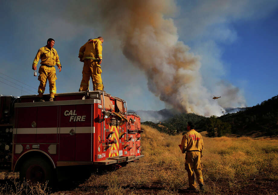 Cal Fire firefighters from Amador, Andrew Paik and Munir Massoud talk with Brian Gobba, right, as they take a break after a full shift of fighting the fire as the Rocky Fire burns off of highway 20 behind and in front of them August 3, 2015 in Lake County, Calif. Photo: Leah Millis / The Chronicle / ONLINE_YES