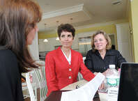Fran Herzog, left, speaks with Diane Blanchard, center, and Debbie Siciliano at the table where Blanchard and Siciliano founded their Lyme Disease advocacy and education organization, Time for Lyme, in Siciliano's Greenwich home. Herzog is a member of the renamed Lyme Research Alliance that is now merging with another Lyme Disease organization.