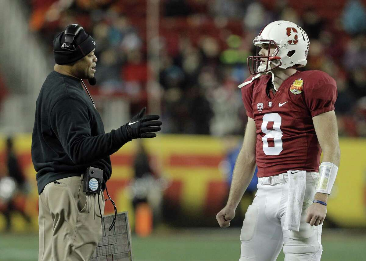 Stanford head coach David Shaw, goes over a play during a timeout with Kevin Hogan in the second period. Stanford Cardinal played the Maryland Terrapins at Levi's Stadium in Santa Clara, Calif., in the 2014 Foster Farms Bowl on Tuesday, December 30, 2014.