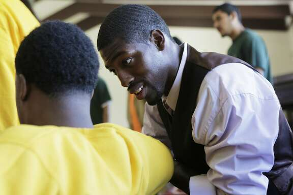 """Juvenile Justice Delinquency Prevention Commissioner Tony Robinson speaks to a young man of Camp Sweeney during the morning pep rally or """"Harambee"""" as a part of Freedom School, a summer program at Camp Sweeney Academic Center, in San Leandro, Ca. on Tuesday, Aug. 4, 2015."""