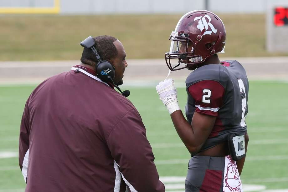 Reagan defensive back Treyvion Waldon talks with head coach Stephen Dixon. Photo: Matthew White, Freelance / Freelance