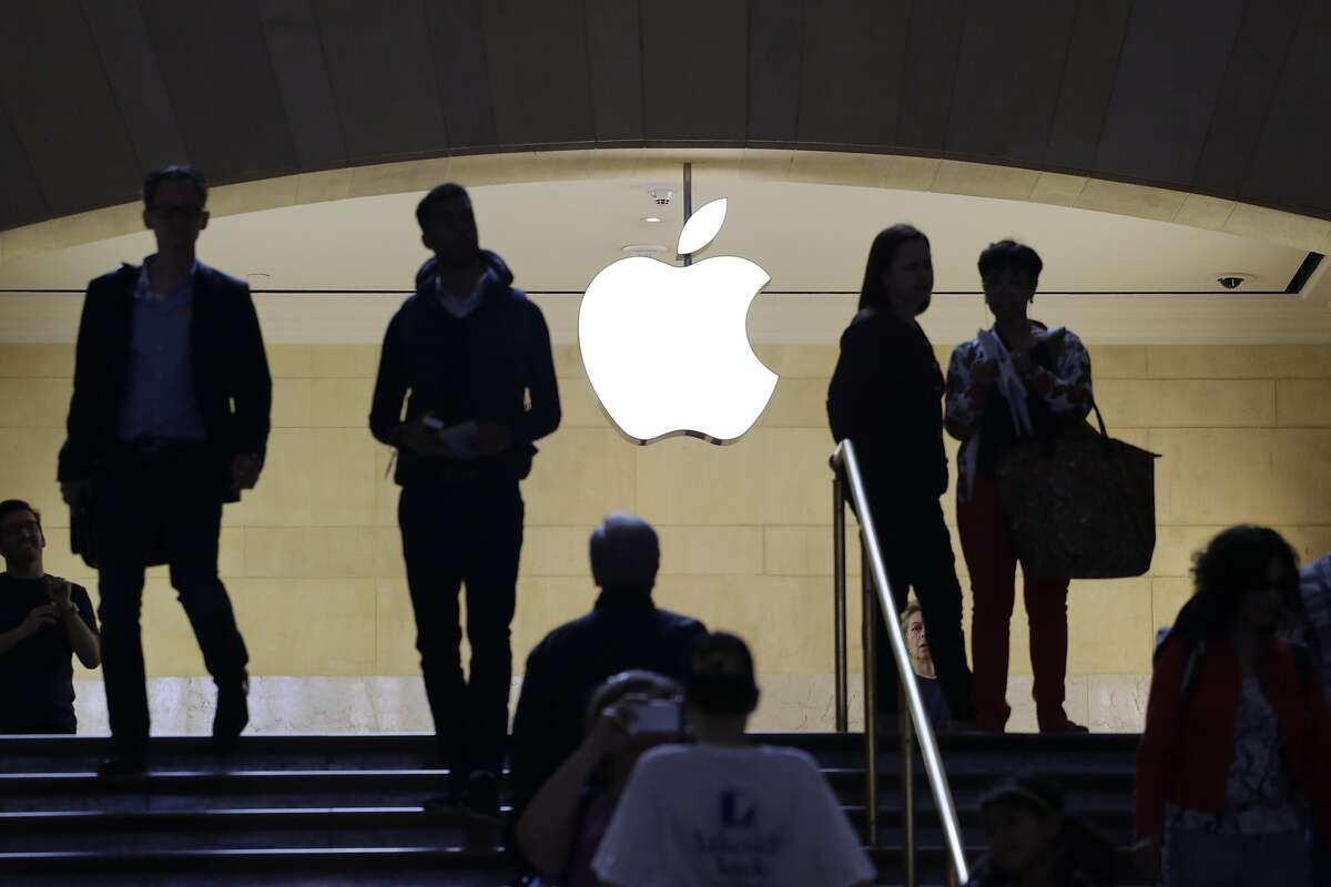 In this May 22, 2015 photo, customers and staff stand in the entrance to an Apple store in New York's Grand Central Terminal. Apple Inc. reports quarterly financial results on Tuesday, July 21, 2015. (AP Photo/Mark Lennihan)