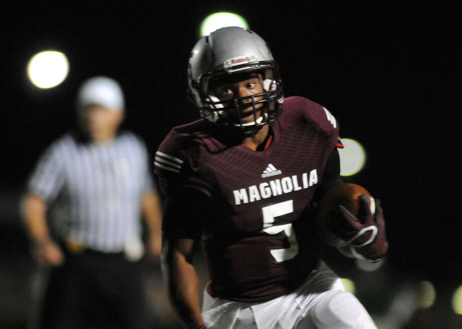 Magnolia freshman running back Anthony Johnson runs for yardage against the Kingwood Park defense during their game at Bulldog Stadium. Photo: Jerry Baker, Freelance