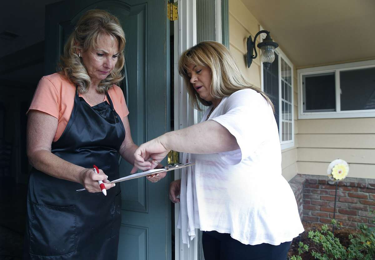 Katherine O'Neal Duran (right) explains a recall effort to a resident in Elk Grove, Calif. on Tuesday, Aug. 4, 2015. The resident, who did not want to give out her name, wanted to research the issue before agreeing to sign the petition. O'Neal Duran is spearheading a recall drive by voters in State Sen. Richard Pan's 6th District, who are angered by the recent passage of a senate bill authored by Pan making vaccinations mandatory in public schools.