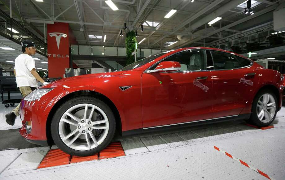 Tesla employees work on a Model S cars in the Tesla factory in Fremont, Calif. San Antonio's zoning commission has voted against Tesla's plan to build a showroom and service center near Shops at La Cantera because of concerns about the city's water supply. Photo: Jeff Chiu /Associated Press / AP