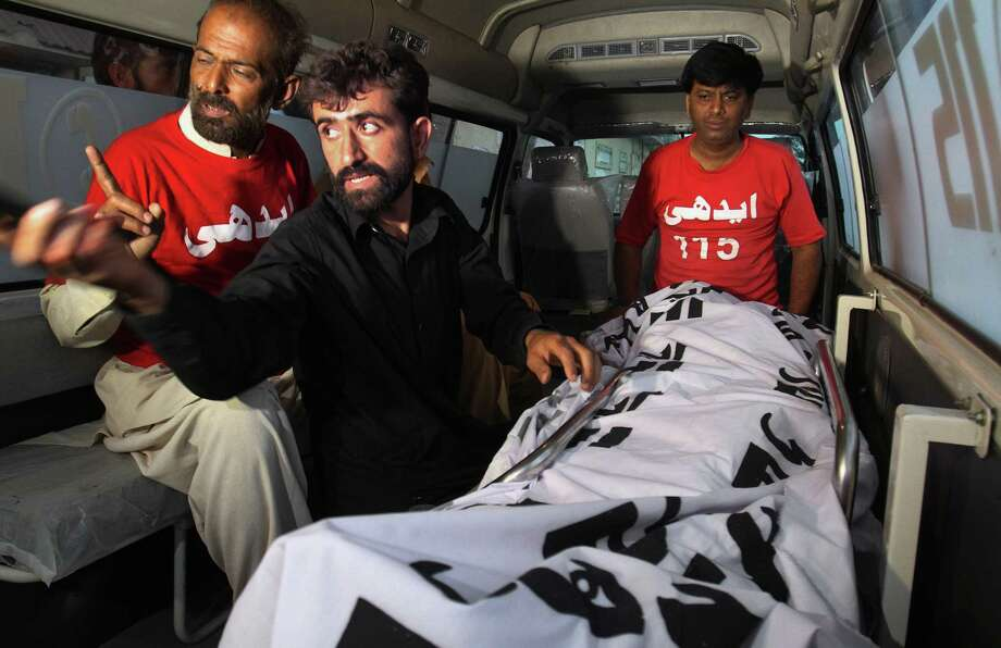 Abdul Majeed, center, sits in front of the lifeless body of his brother Shafqat Hussain. Photo: Fareed Khan / Fareed Khan / Associated Press / AP