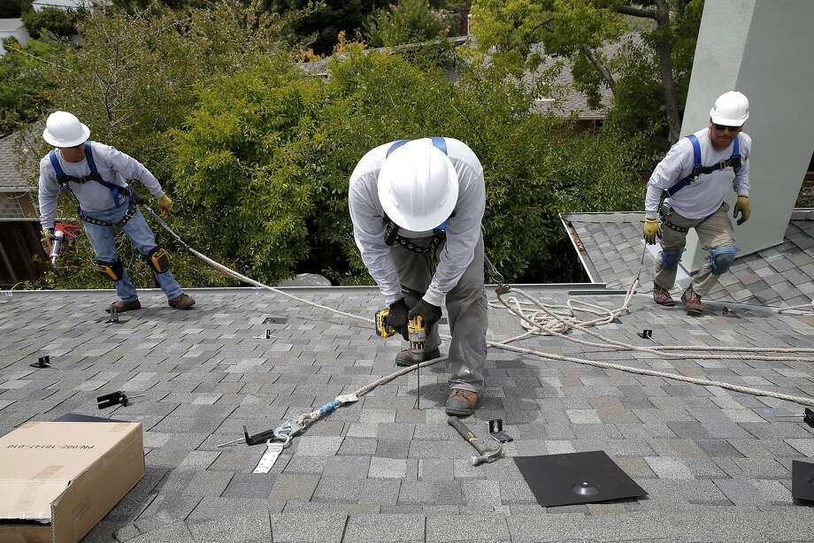 Jonathan Munoz (left), Libni Alonso (center) and Emett Burgos prepare to install new solar panels to a house in Los Gatos, California, on Tuesday, Aug. 4, 2015. Photo: Connor Radnovich, The Chronicle
