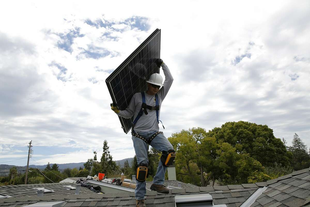 Jonathan Munoz carries a solar panel on the roof of a house in Los Gatos, California, on Tuesday, Aug. 4, 2015.