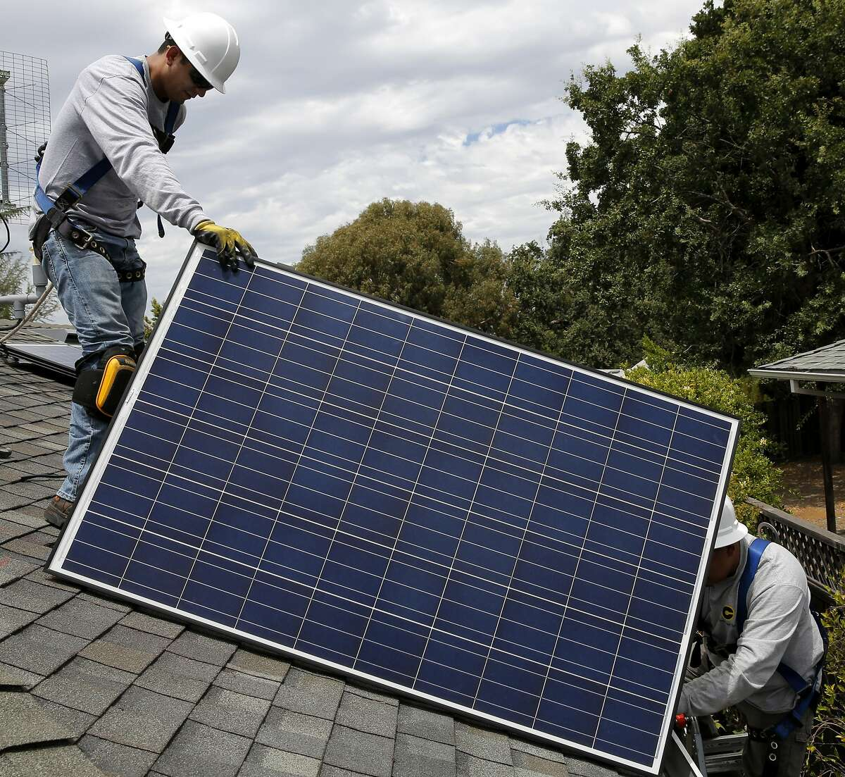Jonathan Munoz holds a solar panel on the roof of a house in Los Gatos, California, on Tuesday, Aug. 4, 2015.