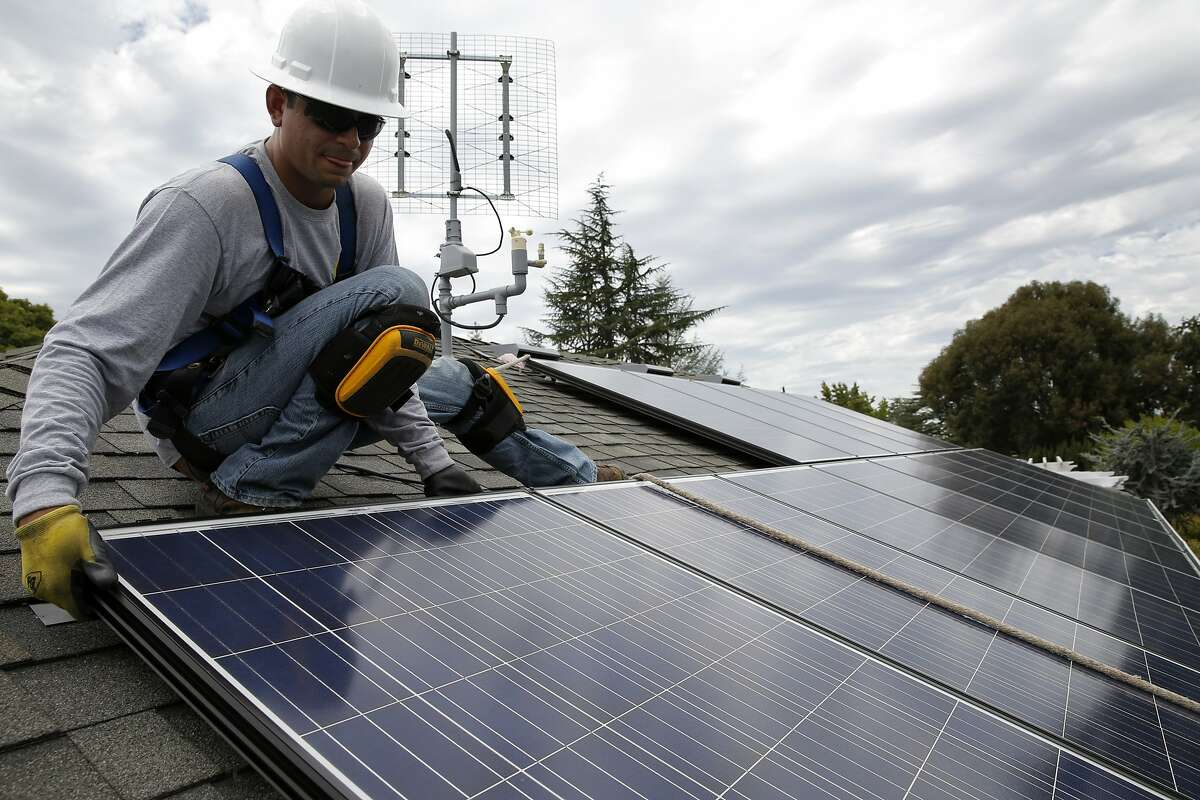 Jonathan Munoz installs a solar panel on the roof of a house in Los Gatos, California, on Tuesday, Aug. 4, 2015.