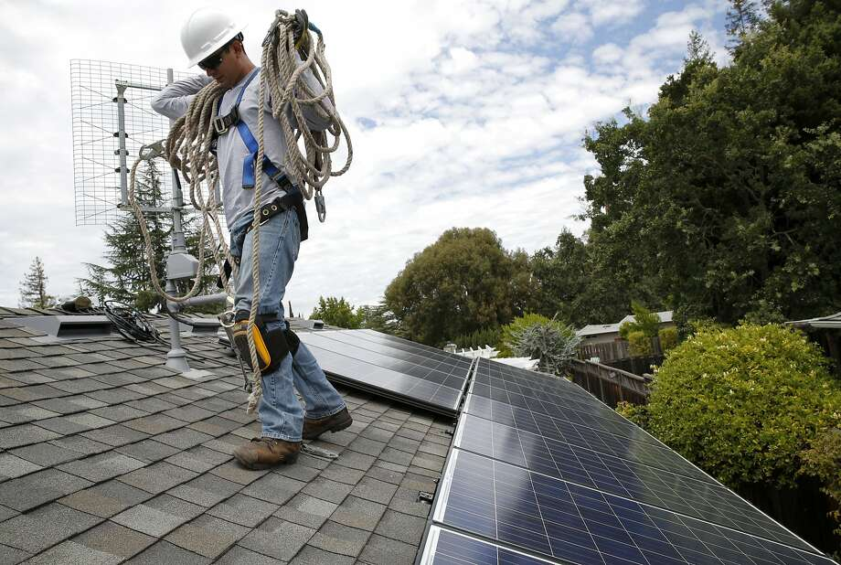 Jonathan Munoz of Cinnamon Solar raises carries safety rope near some newly installed solar panels at a house in Los Gatos, California, on Tuesday, Aug. 4, 2015. Utilities say solar is established, so high incentives aren't needed. Photo: Connor Radnovich, The Chronicle